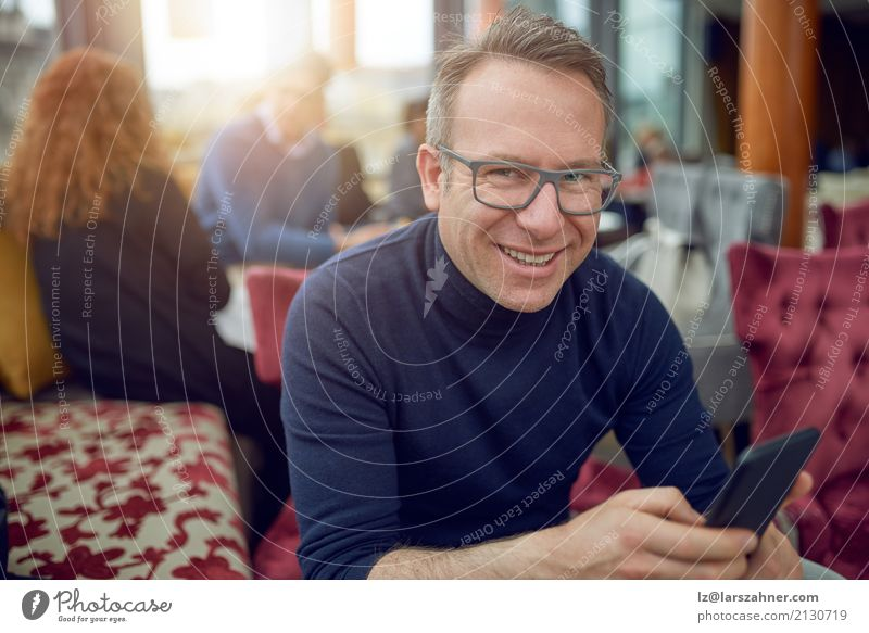 Attractive man sitting in a restaurant Restaurant Business Telephone Cellphone PDA Man Adults 1 Human being 30 - 45 years Eyeglasses Smiling Sit Thin attractive