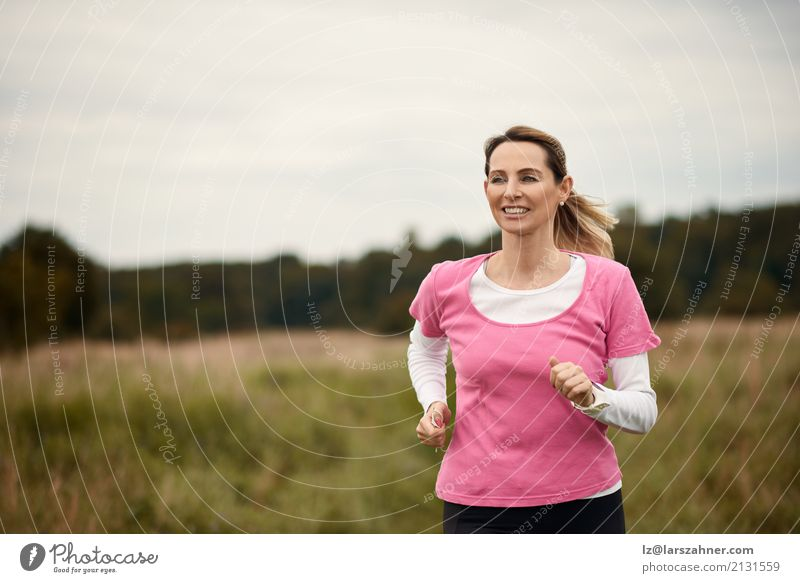 Cheerful woman running through field Human being Woman Nature Summer Face Adults Lifestyle Autumn Sports Copy Space Blonde Action Smiling Fitness Mature Runner