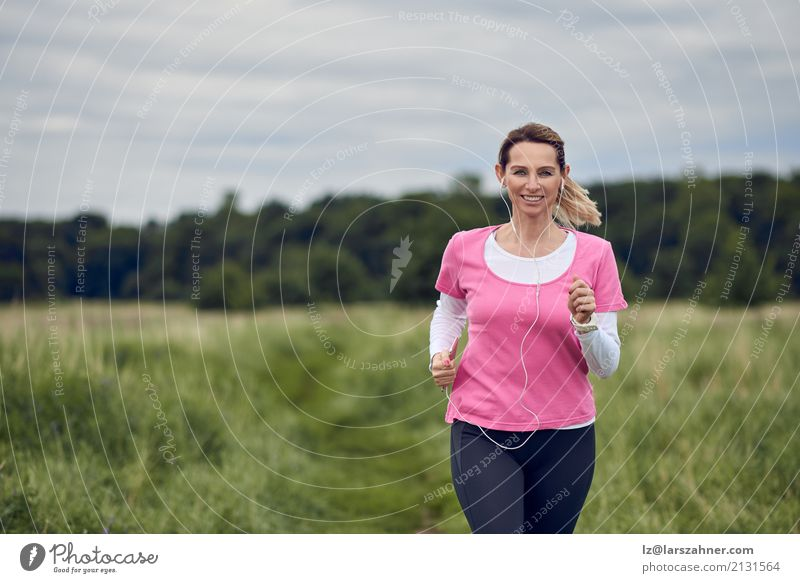 Cheerful woman running through field Human being Woman Nature Summer Face Adults Lifestyle Autumn Natural Sports Copy Space Blonde Music Action Smiling Fitness