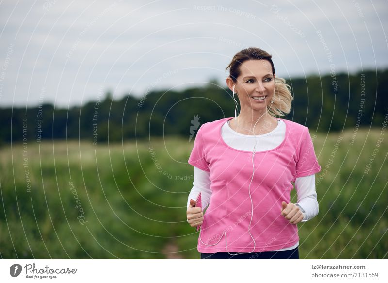 Cheerful woman running through field Lifestyle Face Summer Music Sports Jogging PDA Woman Adults 1 Human being 30 - 45 years Nature Autumn Blonde Fitness