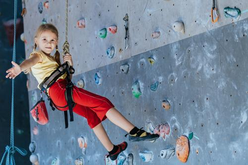 little girl climbing a rock wall indoor. Joy Leisure and hobbies Playing Vacation & Travel Adventure Camping Entertainment Sports Climbing Mountaineering Child