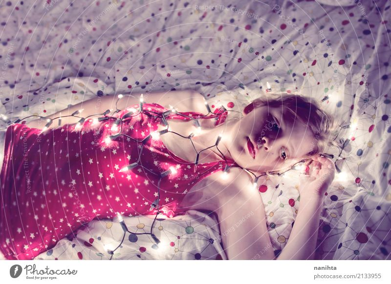 Young woman lying in her bed covered with christmas lights Lifestyle Lamp Bed Bedroom Christmas & Advent New Year's Eve Human being Feminine