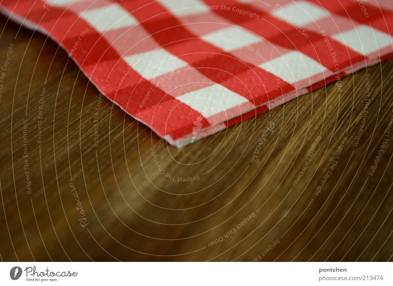A red and white chequered napkin lies on a wooden table. Gastronomy Style Decoration Napkin Kitsch Brown Red White Checkered Wood grain Structures and shapes