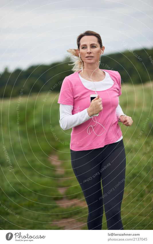 Concentrated woman running through field Human being Woman Nature Summer Face Adults Lifestyle Autumn Sports Copy Space Blonde Music Action Fitness Listening