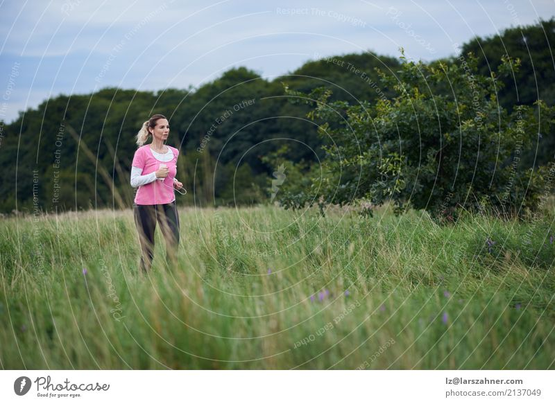 Fit middle-aged woman running through a field Lifestyle Happy Summer Sports Jogging Telephone Cellphone Woman Adults Nature Lanes & trails Blonde Fitness