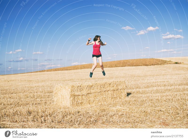 Young woman jumping in a field of harvest wheat Human being Sky Vacation & Travel Youth (Young adults) Blue Summer Joy 18 - 30 years Adults Life Yellow