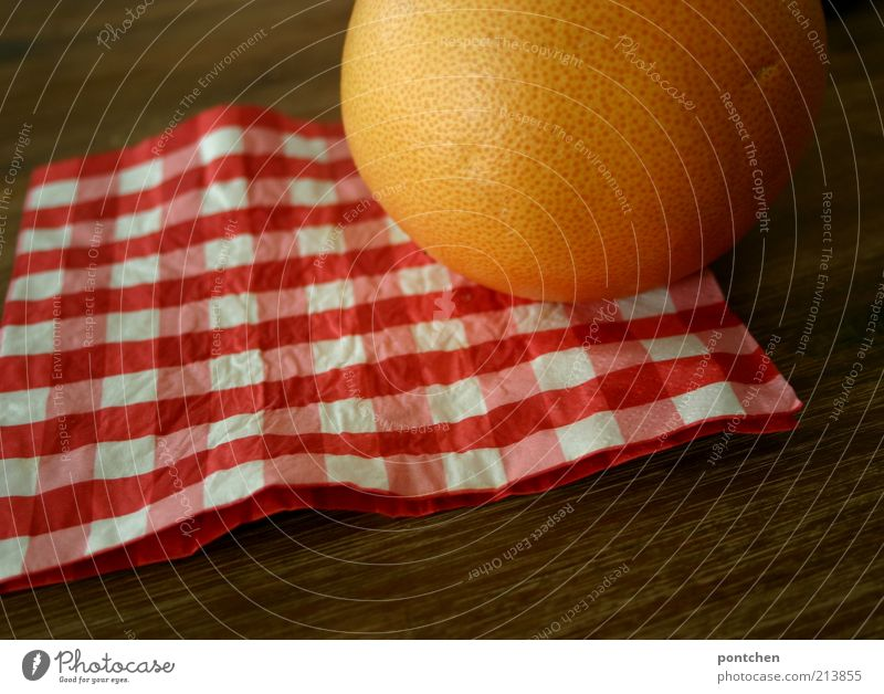 A grapefruit on a red and white checked napkin on a wooden table. Colours and companies. Round and square Food Grapefruit Nutrition Living or residing