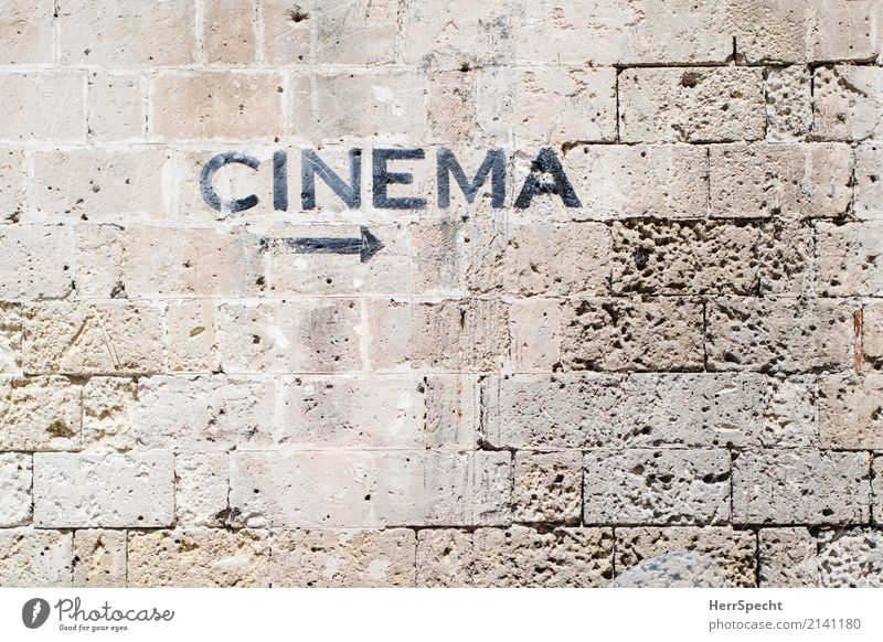 Movies to the right Wall (barrier) Wall (building) Stone Signage Warning sign Arrow Old Esthetic Brown Cinema Film industry Movie hall hint arrow Stone wall