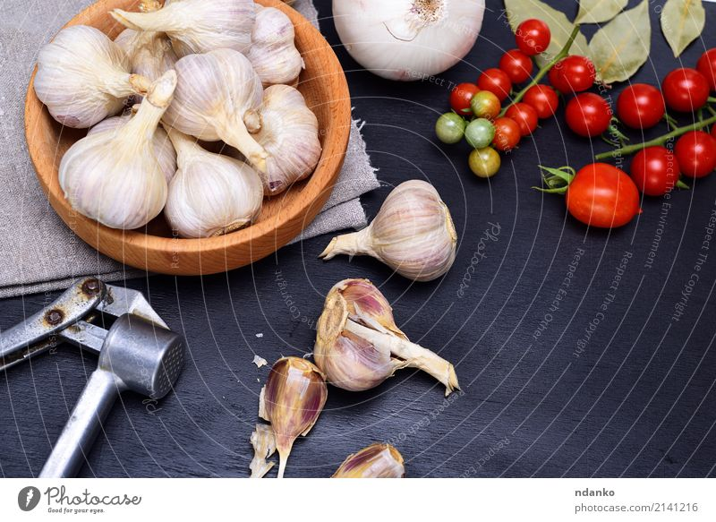 Fresh garlic in a wooden bowl Vegetable Herbs and spices Nutrition Bowl Wood Metal Gray Red Black White Garlic seasoning food Tomato Cherry husk napkin Top