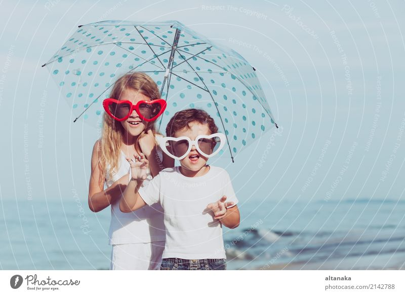Two happy children standing on the beach at the day time. Concept of friendly family. Lifestyle Joy Happy Beautiful Relaxation Leisure and hobbies Playing