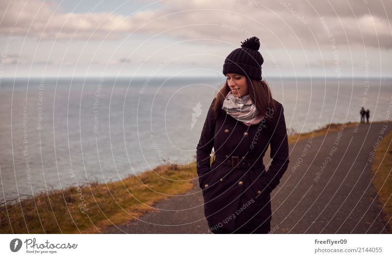 Young woman in winter hiking near the ocean Human being Sky Vacation & Travel Youth (Young adults) Water Landscape Ocean Clouds Joy Far-off places Winter