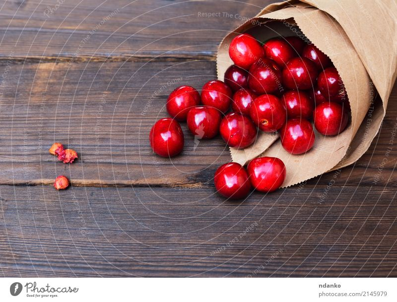 Red cherry in a paper bag Fruit Dessert Eating Vegetarian diet Juice Summer Garden Table Nature Paper Wood Fresh Natural Above Juicy background Berries Cherry