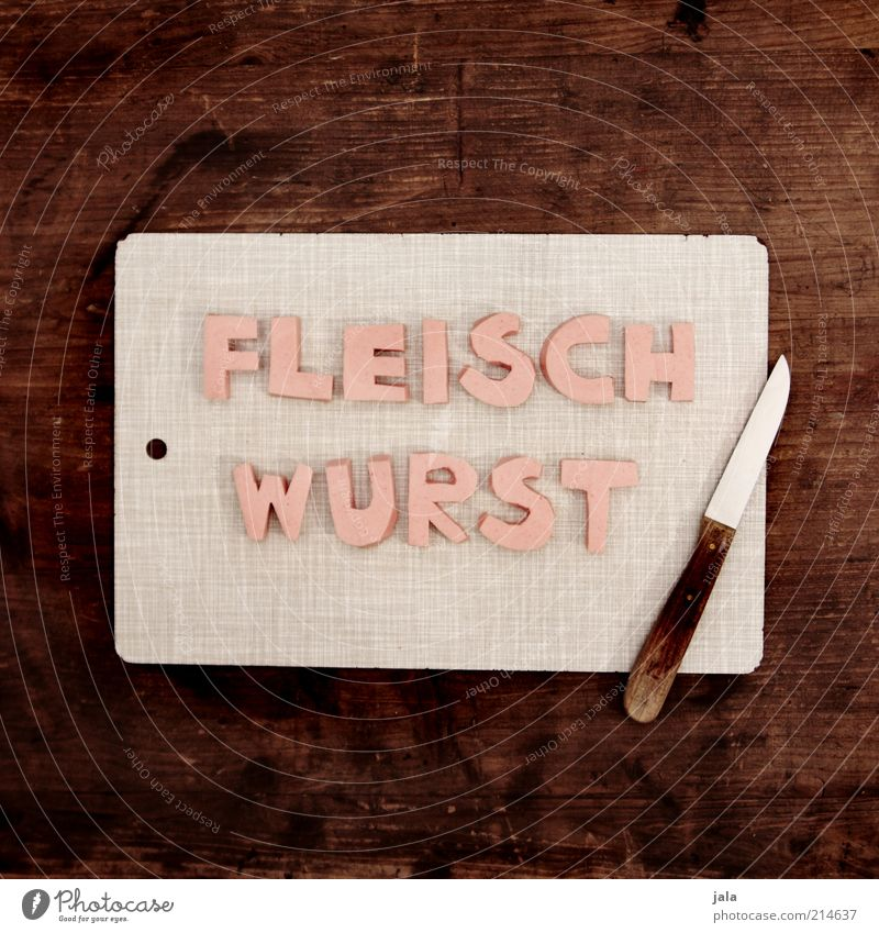 nonsense photograph Food Meat Sausage Nutrition Finger food Knives Chopping board Wood Characters Funny Brown Gray Pink Ham sausage Colour photo Interior shot