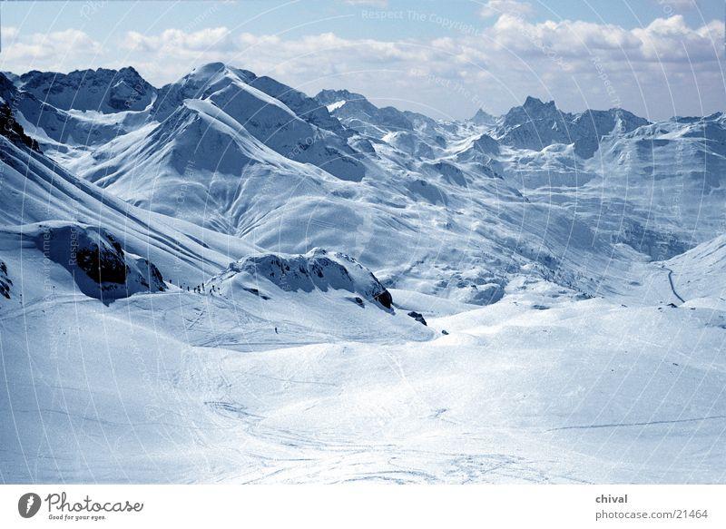 Sky Vacation & Travel Sun Clouds Far-off places Winter Mountain Snow Rock Large Alps Tracks Ski resort Valley Ski run Downward slide