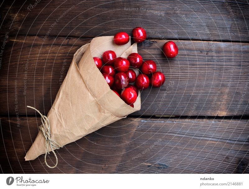 Ripe red cherry in a paper bag Fruit Dessert Eating Vegetarian diet Juice Summer Garden Table Nature Paper Wood Fresh Natural Above Juicy Red background Berries