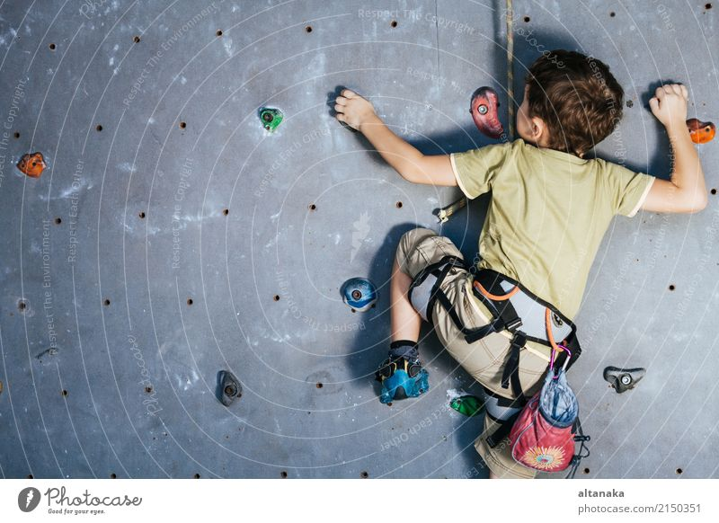 little boy climbing a rock wall indoor. Joy Leisure and hobbies Playing Vacation & Travel Adventure Camping Entertainment Sports Climbing Mountaineering Child