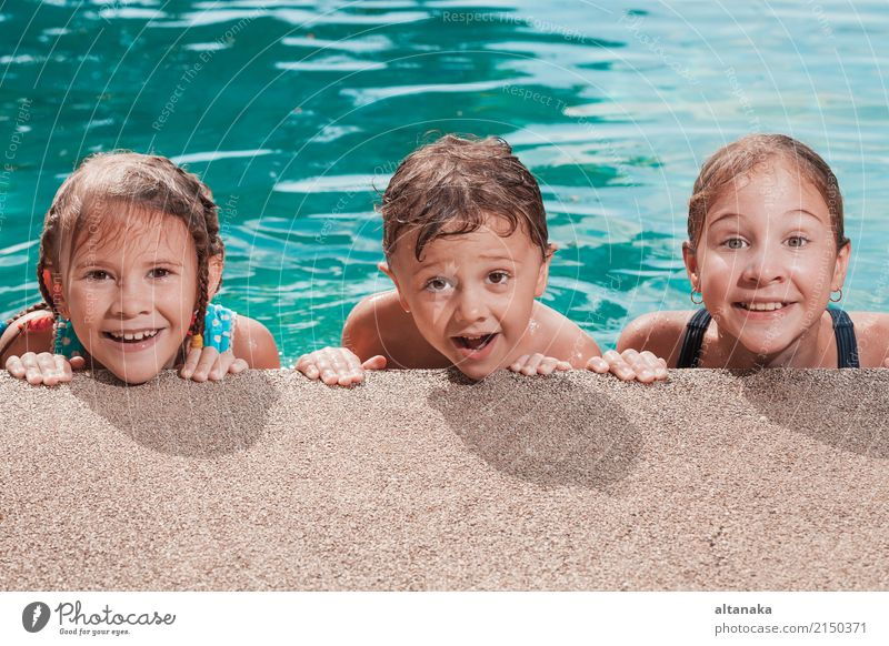 Three happy children playing on the swimming pool at the day time. People having fun outdoors. Concept of friendly siblings. Lifestyle Joy Happy Face Relaxation