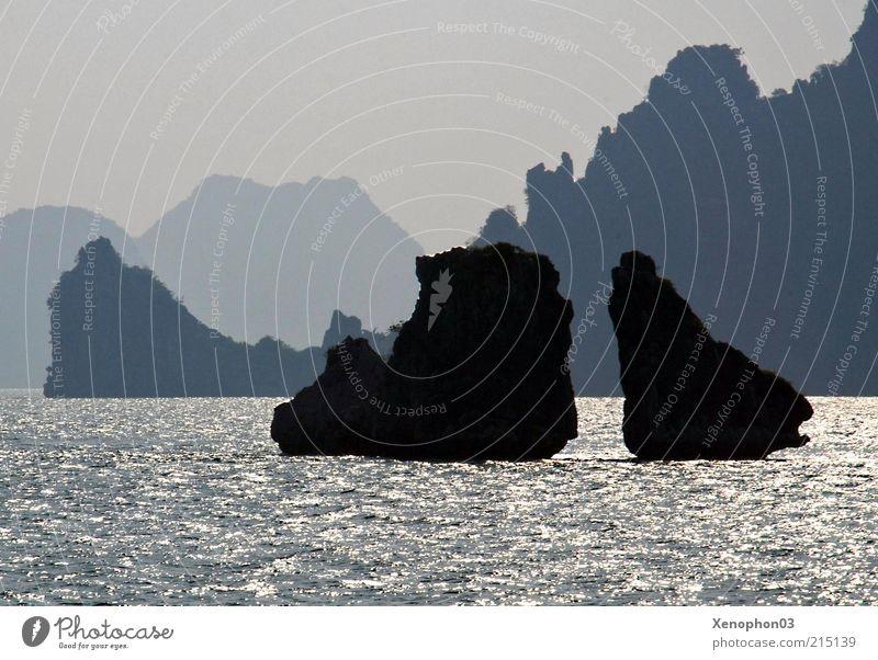 Water Sky Ocean Calm Far-off places Landscape Moody Coast Waves Rock In pairs Island Romance Hill Peak