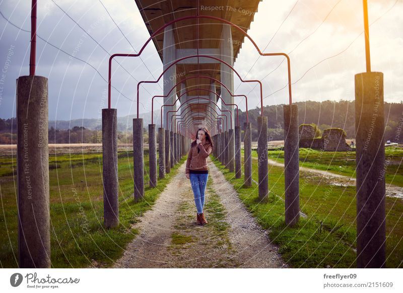 Young girl posing under a bridge in the nature Human being Vacation & Travel Youth (Young adults) Young woman Landscape Joy Far-off places Winter 18 - 30 years
