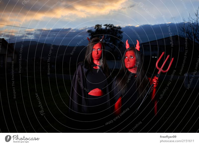 Two woman disguised as devils in the dark Lifestyle Cosmetics Make-up Facial painting Bodypainting Leisure and hobbies Playing Disguised Carnival