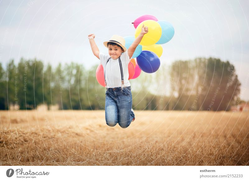 Boy jumping with balloons in the field Lifestyle Joy Vacation & Travel Adventure Freedom Summer vacation Child Toddler Infancy 3 - 8 years Meadow Field To enjoy