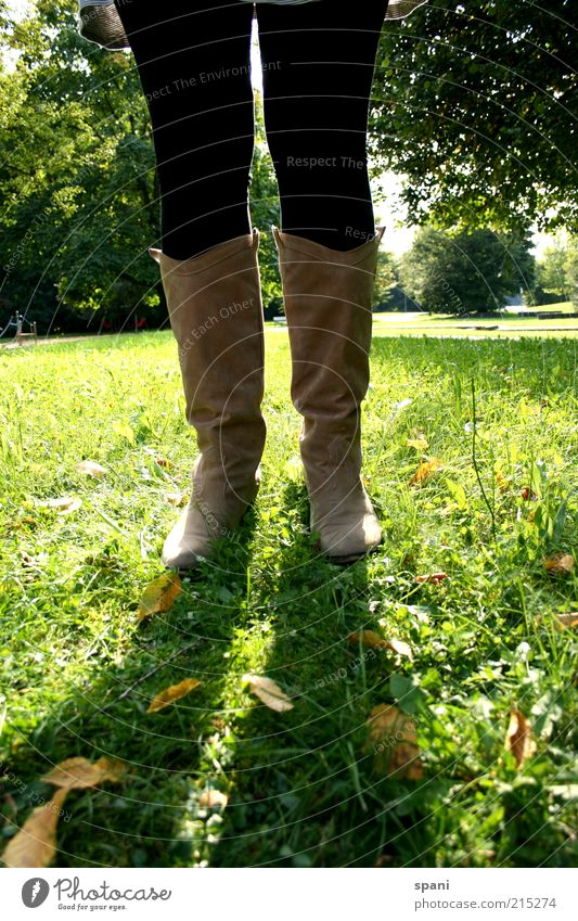 sunblock Legs Feet 1 Human being Summer Park Meadow Stand Self-confident Calm Leisure and hobbies Boots Tights Sunlight Green Back-light Multicoloured