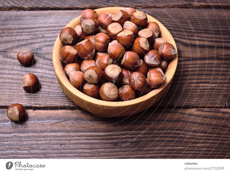 Hazelnuts in a shell Nature Old Autumn Natural Wood Brown Above Fruit Nutrition Fresh Table Strong Bowl Plate Vegetarian diet Rough