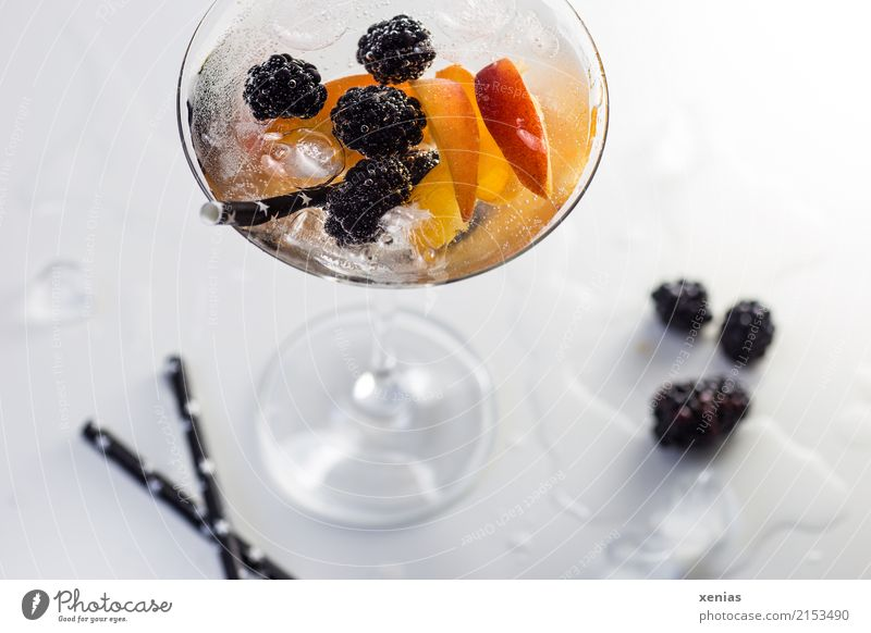 Refreshing drink full of vitamins in a cocktail glass with blackberries, nectarine, ice cubes and drinking straw Beverage Blackberry Nectarine Ice cube