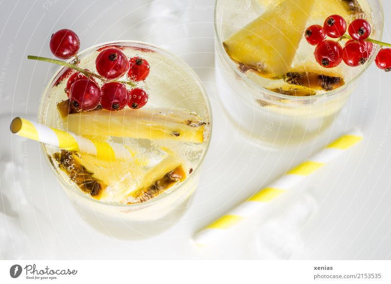 Refreshing drink with pineapple, currants, yellow drinking straws and ice cubes on a white background Beverage Cold drink Pineapple Redcurrant Ice cube