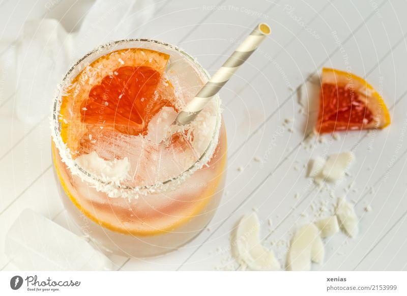Fresh grapefruit with coconut rasps in water Fruit Grapefruit Coconut Ice cube Organic produce Vegetarian diet Beverage Cold drink Drinking water Lemonade Glass