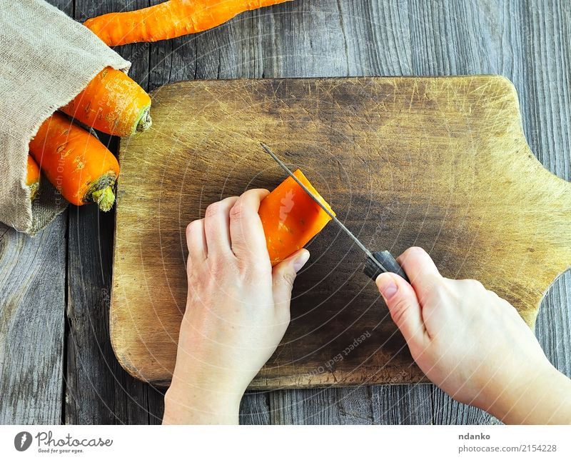 Two female hands with a knife Food Vegetable Eating Knives Body Kitchen Woman Adults Hand Fresh Gray Carrot orange part board cooking slicing Harvest health Raw