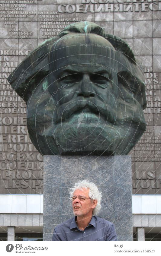 male senior with silver-grey curls, glasses and three-day beard sitting in front of the Karl Marx monument in Chemitz Human being Masculine Male senior Man