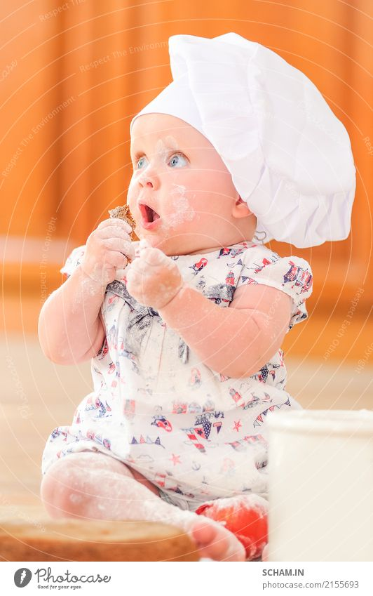 A cute little girl in chef's hat sitting on the kitchen floor soiled with flour, playing with food, making a mess and having fun Food Cake Eating Lifestyle Joy