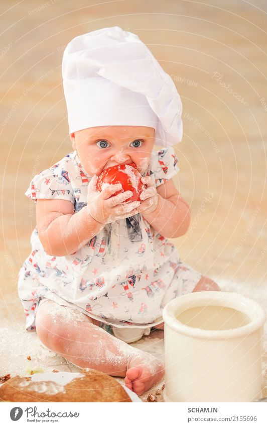 A cute little girl in chef's hat sitting on the kitchen floor soiled with flour, playing with food, making a mess and having fun Eating Lifestyle Joy Feminine