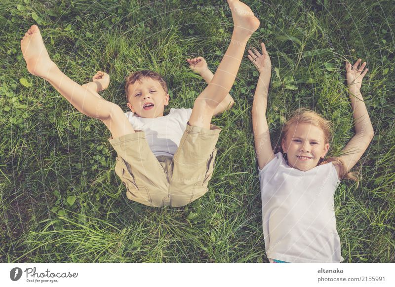 Two happy children playing on the grass at the day time. Concept Brother And Sister Together Forever Lifestyle Joy Happy Beautiful Face Leisure and hobbies