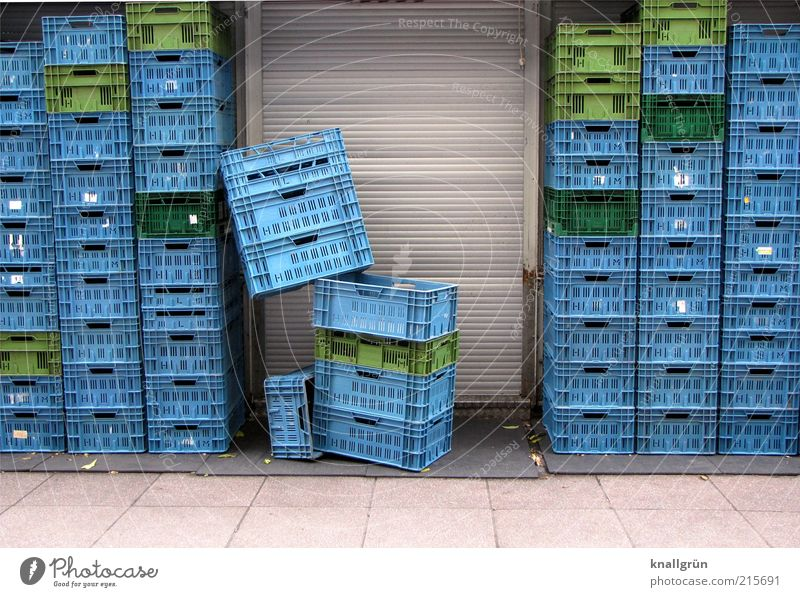 consumption Door Roller shutter Sharp-edged Tall Blue Gray Green Arrangement Supermarket transport box Plastic basket Stack Colour photo Exterior shot Deserted