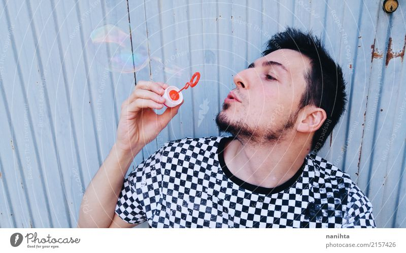 Young man playing with soap bubbles Human being Youth (Young adults) Blue White Relaxation 18 - 30 years Black Adults Lifestyle Funny Style Playing