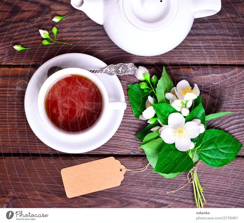 hot black tea in a white cup Breakfast Beverage Tea Spoon Table Flower Leaf Wood Fresh Hot Above Retro Brown Green Black White Tradition Jasmine drink food Top