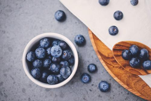 Top view of organic fresh blueberries Fruit Nutrition Breakfast Organic produce Diet Bowl Spoon Healthy Eating Paper Wood Fresh Delicious Natural White