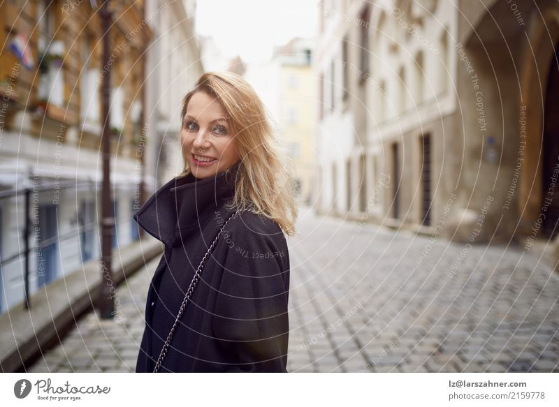 Attractive woman standing outdoors in a courtyard Skin Face Woman Adults 1 Human being 30 - 45 years Pedestrian Street Blonde Smiling Historic Cute attractive