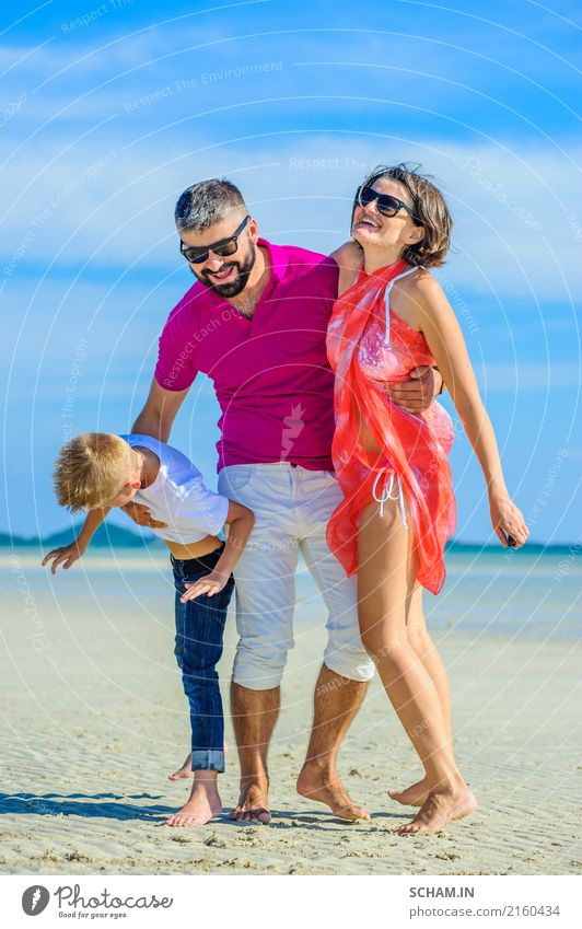 Happy family of three at the tropical beach, laughing and enjoying time together. Lifestyle Joy Playing Summer Ocean Island Infancy Landscape Sunglasses Beard