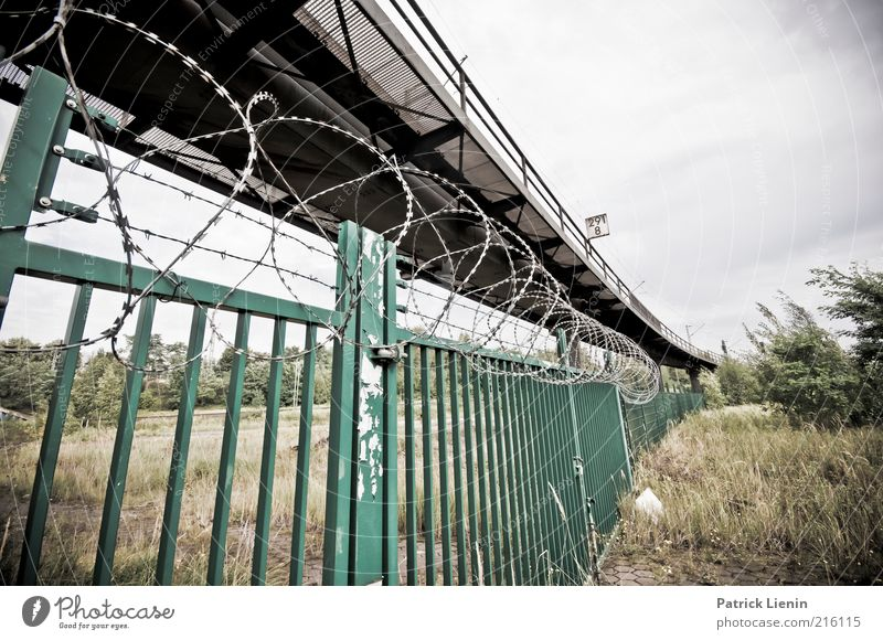 locked and excluded Looking Moody Fear Railroad tracks Fence Barbed wire Gate Barrier Bridge Commuter trains Grass Closed Dangerous Bans Protest New building