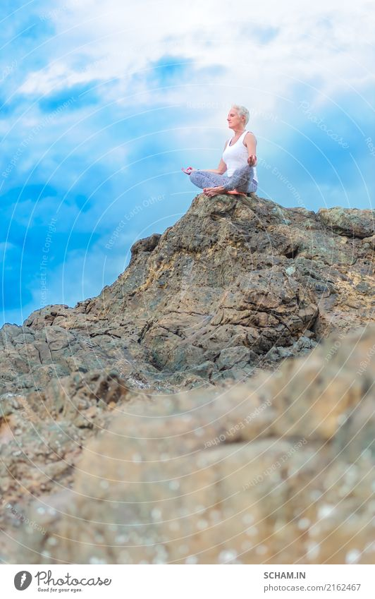 Beautiful mature aged woman sits on top of a cliff doing yoga Human being Woman Sky Nature Old Blue Summer Landscape Relaxation Clouds Calm Joy Far-off places