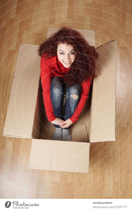 young woman sits in moving box Lifestyle Joy Happy Living or residing Flat (apartment) Moving (to change residence) Human being Feminine Girl Young woman