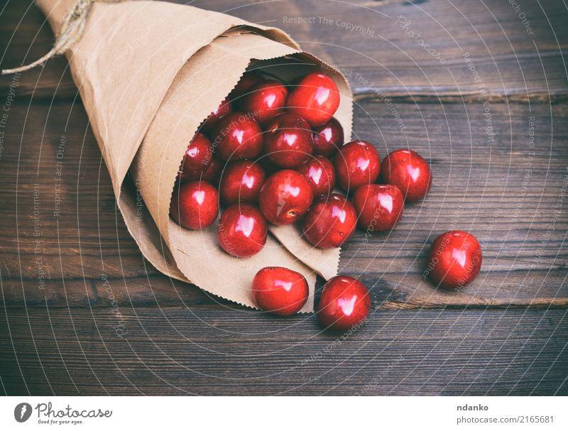 red cherry in a paper bag Fruit Dessert Eating Vegetarian diet Juice Summer Garden Table Paper Wood Fresh Natural Retro Juicy Brown Red background Berries