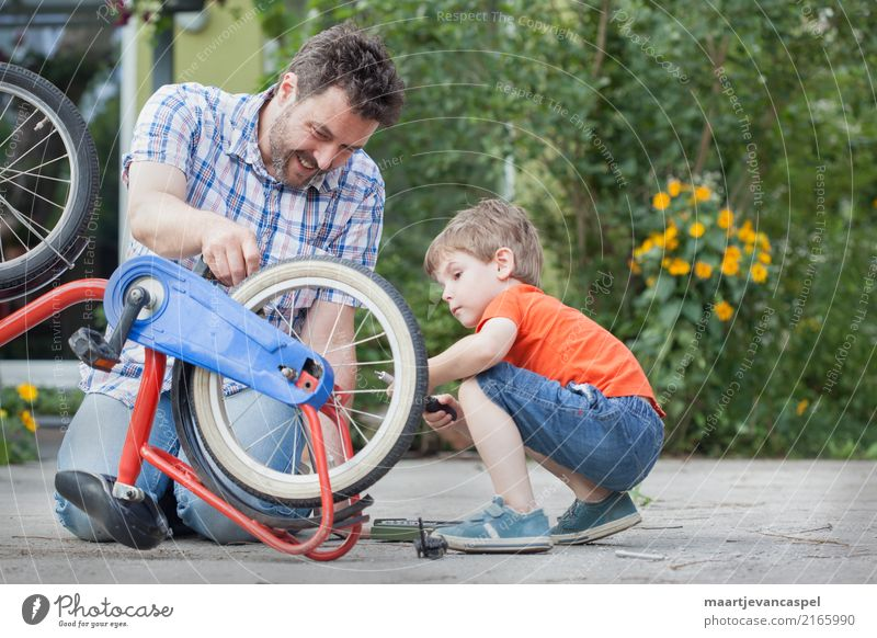 Father and son repair a bicycle together Lifestyle Leisure and hobbies Handicraft Repair Bicycle Garden Human being Masculine Child Boy (child) Man Adults