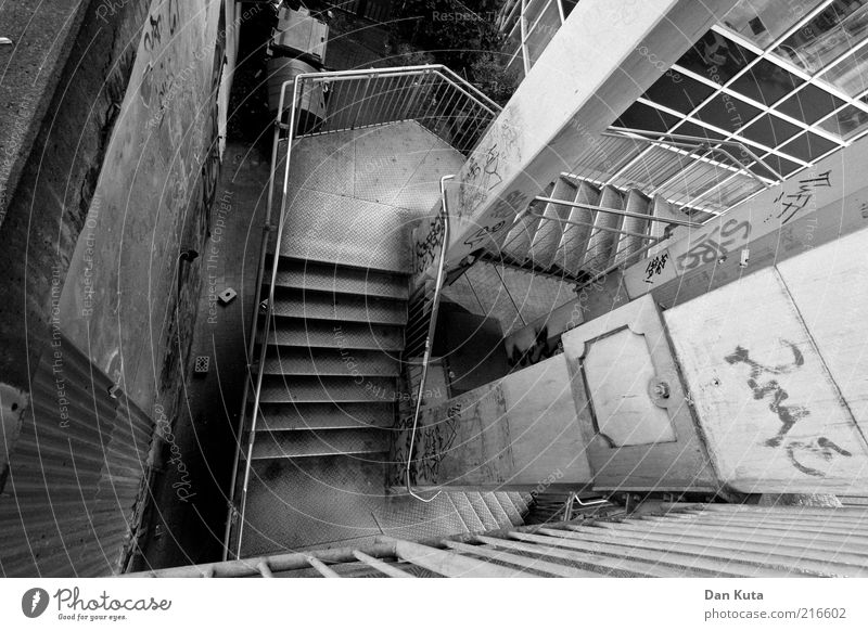 Backstreet Deserted Manmade structures Stairs Stair tower Handrail Banister Authentic Downward Story Dirty Concrete Column Graffiti Daub Black & white photo