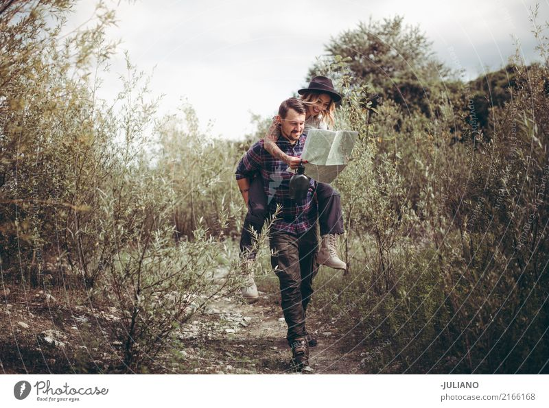 sweet couple making piggyback while looking at map Child Human being Nature Vacation & Travel Youth (Young adults) Joy Far-off places Environment Lifestyle Love