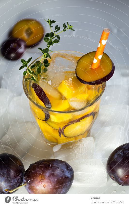 Iced soft drink with plum, mango, thyme, ice cubes and drinking straw Beverage Cold drink Plum Mango Thyme Ice cube fruit Organic produce Vegetarian diet