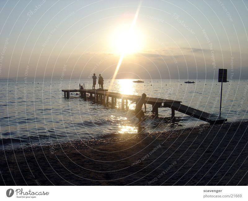 Sunset at Lake Garda Sunbeam White Light Evening sun Sunrise Dark Waves Watercraft Beach Footbridge Horizon Wood Romance Lighting Blue Bright Sky Orange